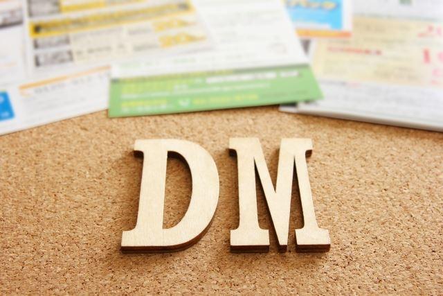 コルクボードの上にあるdmと書かれたロゴ/DM発送代行・宛名シール貼り付け・印刷ならお任せ!料金の問い合わせはお気軽に 依頼する際に確認すること