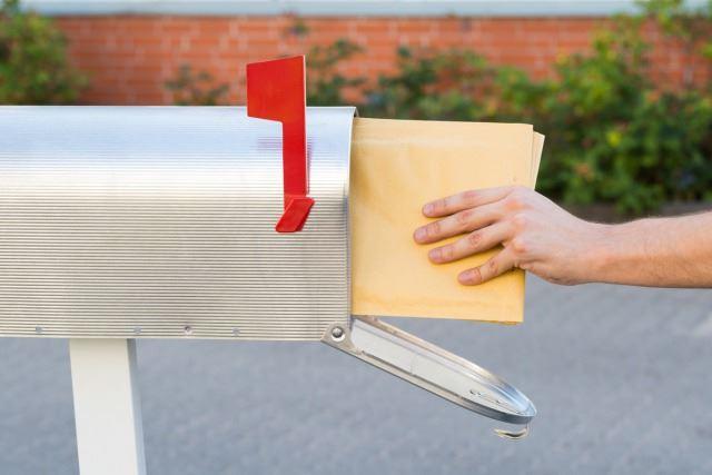 シルバーの郵便受けに投函される郵便物