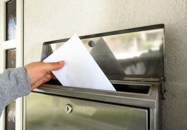 シルバーの郵便受けに投函された白い封筒/
