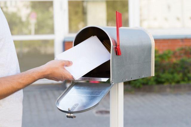 小さなシルバーの郵便受けに投函された郵便物/